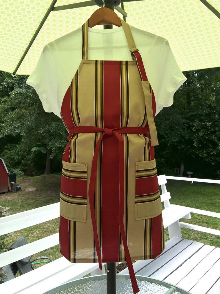 Chef's apron featuring large stripes in brick red and sand beige.