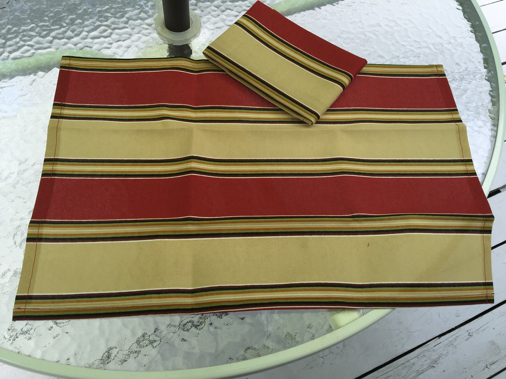 Decorative towels featuring large stripes in brick red and sand beige.